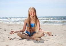 De zitting van het meisje op strand Stock Afbeelding