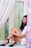 De zitting van het meisje op venstervensterbank Stock Afbeelding