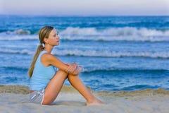 De zitting van het meisje op wit zand op het strand royalty-vrije stock fotografie