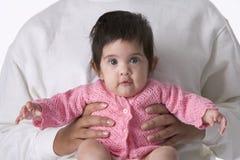 De Zitting van het Meisje van de baby op de Overlapping van Moeders Stock Foto