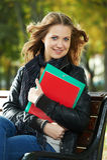 De zitting van het Meisje van de student op bank in openlucht Stock Foto's