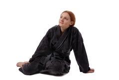 De zitting van het meisje in zwarte eenvormig royalty-vrije stock foto's