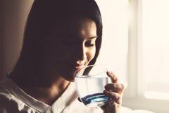 De zitting van het meisjes drinkwater op een laag thuis stock foto's