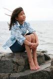 De zitting van het negen éénjarigenmeisje door meer Royalty-vrije Stock Fotografie