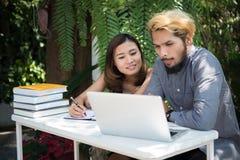 De zitting van het onderwijspaar bij de tuin van het aardhuis, tijd aan lezing stock foto's