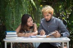 De zitting van het onderwijspaar bij de tuin van het aardhuis, tijd aan lezing stock fotografie