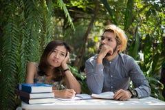De zitting van het onderwijspaar bij de tuin van het aardhuis, tijd aan lezing royalty-vrije stock afbeeldingen