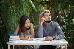 De zitting van het onderwijspaar bij de tuin van het aardhuis, tijd aan lezing royalty-vrije stock foto