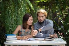 De zitting van het onderwijspaar bij de tuin van het aardhuis, tijd aan lezing stock afbeelding