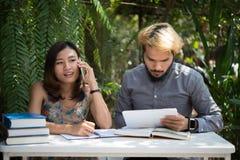 De zitting van het onderwijspaar bij de tuin van het aardhuis, tijd aan lezing royalty-vrije stock afbeelding