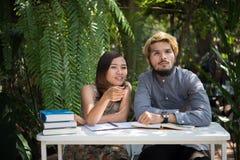 De zitting van het onderwijspaar bij de tuin van het aardhuis, tijd aan lezing royalty-vrije stock fotografie
