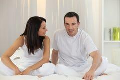 De zitting van het paar in bed Stock Foto's