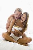 De zitting van het paar in bed dat graangewas en het glimlachen eet royalty-vrije stock foto