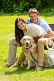 De zitting van het paar met gouden retriever in park Stock Fotografie