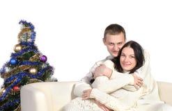 De zitting van het paar op bank dichtbij Kerstboom Stock Foto's