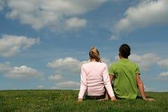 De zitting van het paar op het gras Stock Fotografie