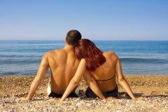 De zitting van het paar op het strand stock fotografie