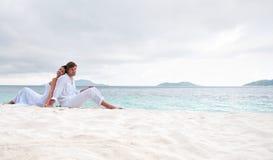 De zitting van het paar op het strand dichtbij de kust Stock Afbeelding
