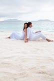 De zitting van het paar op het strand dichtbij de kust Royalty-vrije Stock Foto's