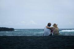 De zitting van het paar op het zand stock fotografie