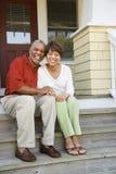 De Zitting van het paar op OpenluchtStappen van het Glimlachen van het Huis Royalty-vrije Stock Foto