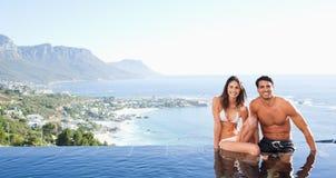 De zitting van het paar op poolrand met landschap stock fotografie