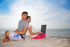 Paarzitting op strand het ontspannen stock foto
