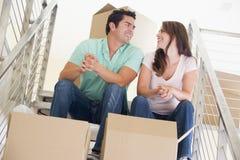 De zitting van het paar op trap met dozen in nieuw huis stock foto's