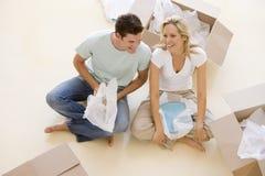 De zitting van het paar op vloer door open dozen in nieuw huis stock afbeeldingen