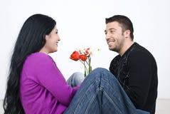 De zitting van het paar op vloer en het lachen Stock Fotografie