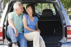 De zitting van het paar in rug van bestelwagen het glimlachen Royalty-vrije Stock Foto