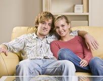 De zitting van het paar samen op bank Royalty-vrije Stock Afbeeldingen