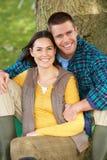 De zitting van het paar tegen boomboomstam Stock Afbeelding