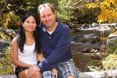 De zitting van het Paar van Romatic door een Stroom stock fotografie