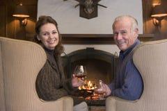 De zitting van het paar in woonkamer door open haard royalty-vrije stock fotografie