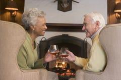 De zitting van het paar in woonkamer door open haard stock foto's