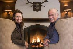 De zitting van het paar in woonkamer door open haard te glimlachen royalty-vrije stock foto