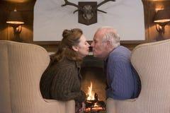 De zitting van het paar in woonkamer door open haard te kussen stock fotografie