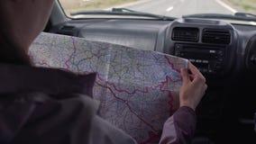 De zitting van het reizigersmeisje in de drijfauto die kaart en vindt de manier kijken stock footage