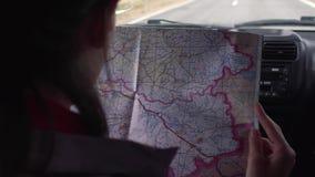 De zitting van het reizigersmeisje in de drijfauto die kaart en vindt de manier kijken stock videobeelden