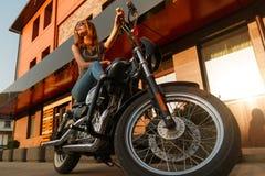 De zitting van het roodharigemeisje op een motorfiets stock foto