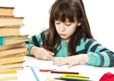 De zitting van het schoolmeisje en het schrijven in notitieboekje royalty-vrije stock fotografie