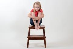 De zitting van het schoonheidsmeisje op een kruk Stock Foto's