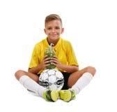 De zitting van het sportenjonge geitje met een bal op een witte achtergrond wordt geïsoleerd die Schooljongen en een groene smoot Stock Fotografie