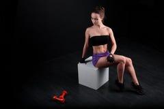 De zitting van het sportmeisje en het bekijken domoor op zwarte achtergrond Royalty-vrije Stock Fotografie