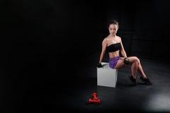 De zitting van het sportmeisje en het bekijken domoor op zwarte achtergrond Royalty-vrije Stock Afbeeldingen