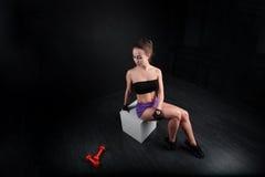 De zitting van het sportmeisje en het bekijken domoor op zwarte achtergrond Stock Afbeeldingen