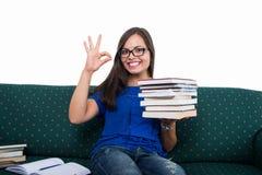 De zitting van het studentenmeisje op laag die o.k. holdingsboeken tonen stock foto