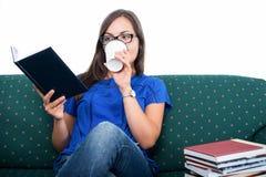 De zitting van het studentenmeisje op laaglezing het drinken koffie stock afbeeldingen