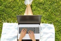 De zitting van het studentmeisje op het groene gazon die thuiswerk op haar laptop computer doen Jonge vrouwenzitting bij het park royalty-vrije stock fotografie